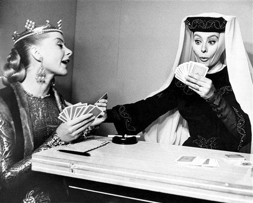 "In her true dramatic style, Sophia Lore, right, registers surprise as she looks at her cards while battling it out with Genevieve Page in a game of gin rummy. Wearing their play costumes, the Italian and French stars played between takes of ""El Cid,"" on location in Spain on Nov. 17, 1961. (AP Photo)"