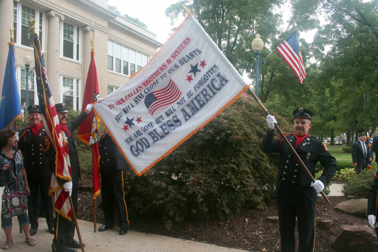 East Wallingford firefighters Steve Brooks and Hugh Kline hold a memorial flag of a sign that