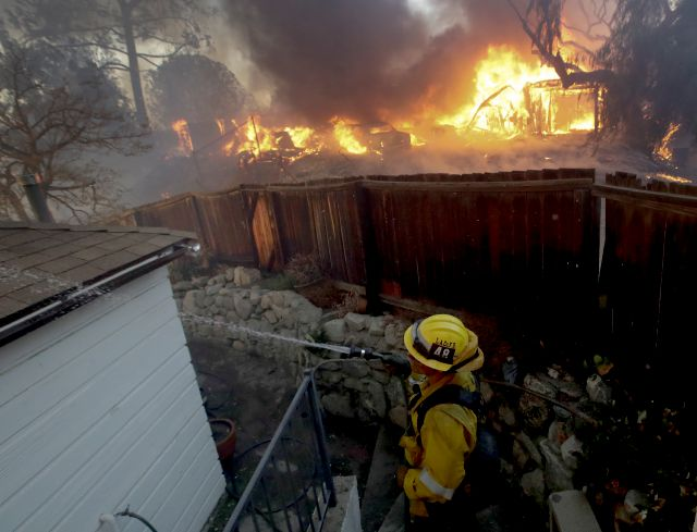 A Los Angeles County firefighter puts water on a burning roof during a wildfire in the Lake View Terrace area of Los Angeles Tuesday, Dec. 5, 2017. Ferocious winds in Southern California have whipped up explosive wildfires, burning a psychiatric hospital and scores of other structures. Tens of thousands of people have been ordered evacuated.  (AP Photo/Chris Carlson)