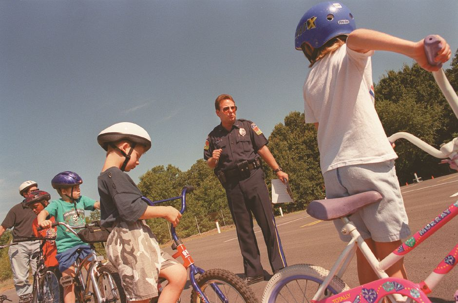 RJ file photo - Drug Abuse Resistance Education officer John Shalkey, who organized the event, offers the helmeted youths bicycle safety tips during the fifth annual Townwide Bicycle Safety Rodeo at Cytec Industries, Aug. 9, 1998.