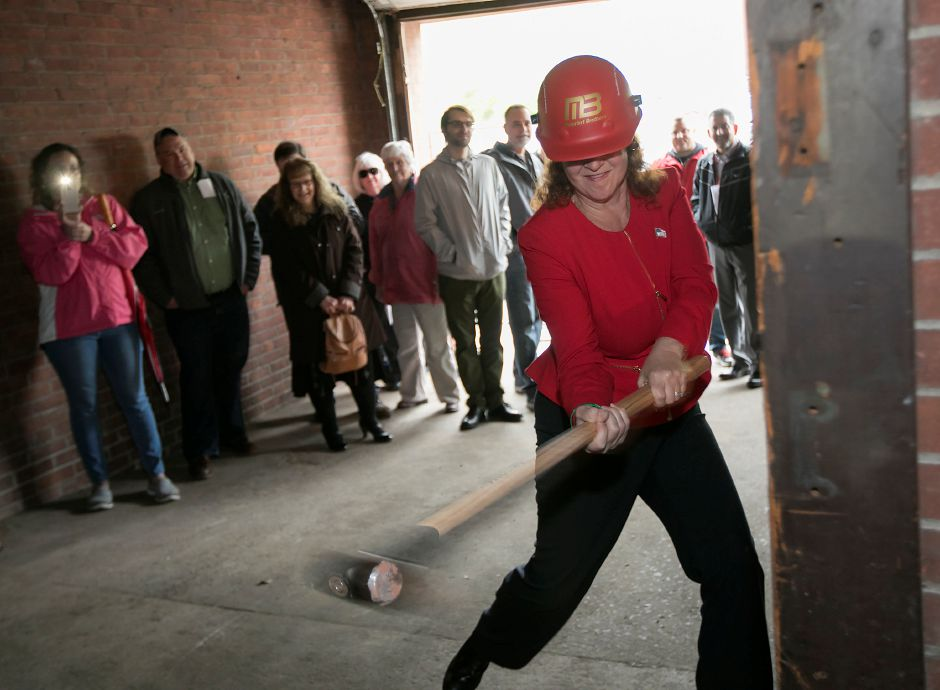 Congresswoman Elizabeth Esty swings a sledgehammer at a brick pillar during a demolition ceremony in the garage of the former Record-Journal building at 11 Crown St. in Meriden, Friday, May 5, 2017. The building served as the headquarters for the Record-Journal newspaper for over a century. | Dave Zajac, Record-Journal