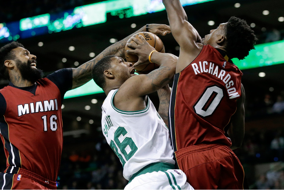 Miami Heat forward James Johnson (16) and guard Josh Richardson (0) try to block Boston Celtics guard Marcus Smart (36) as he drives toward the basket during the first quarter of an NBA basketball game, Sunday, March 26, 2017, in Boston. (AP Photo/Steven Senne)