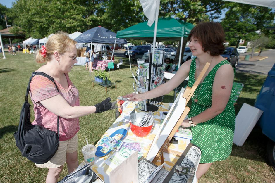 Mary Ellen Crawford of Wallingford left makes a purchase from local artist Amy McNamara Saturday during opening weekend of the Wallingford Garden Market at Doolittle Park in Wallingford June 30, 2018 | Justin Weekes / Special to the Record-Journal