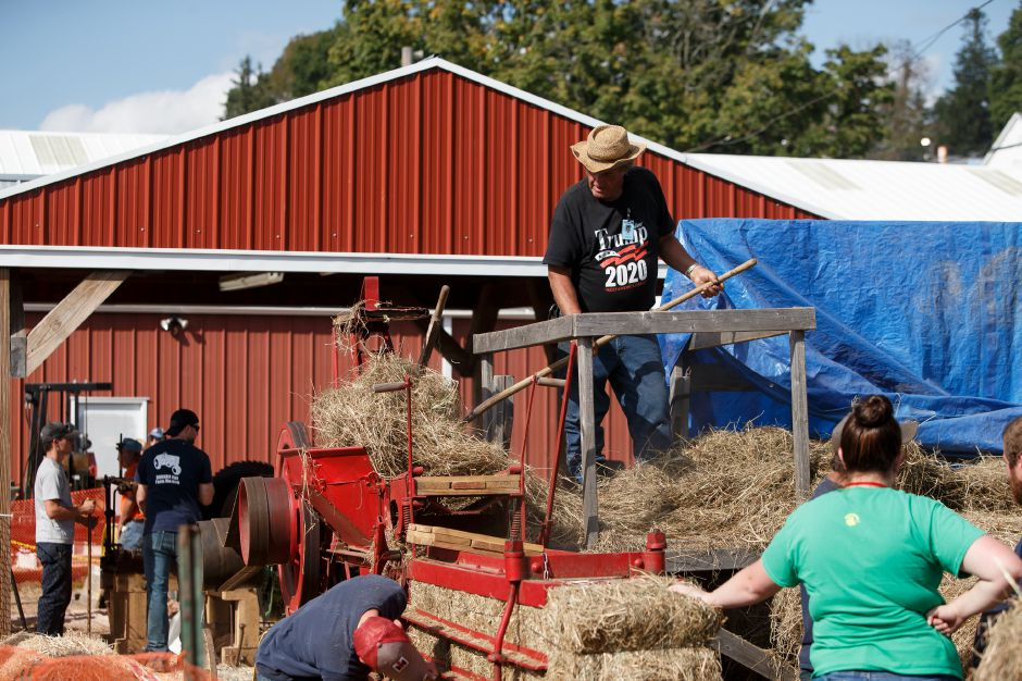 Harold Graves feeds hay into a 1900 Hay Press Saturday during the 99th Durham Fair on the Durham Fairgrounds in Durham September 29, 2018 | Justin Weekes / Special to the Record-Journal