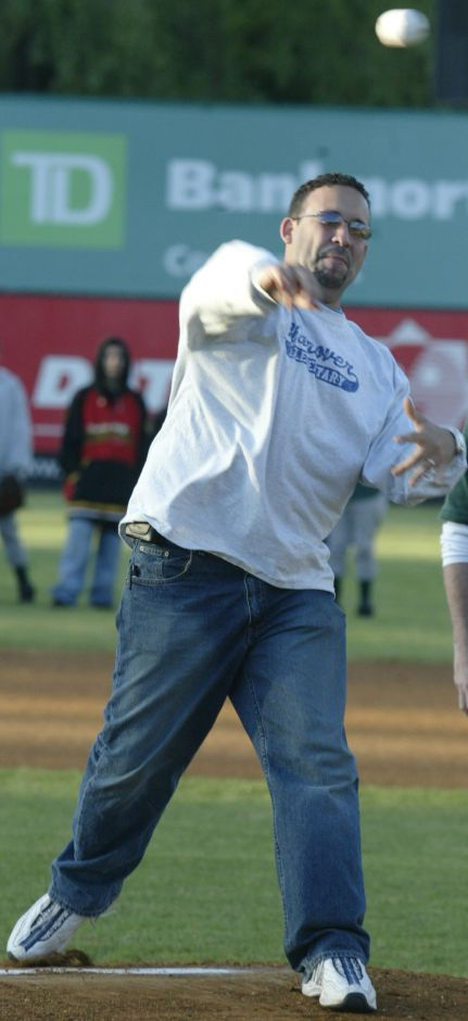 Miguel Cardona, principal of Hanover Elementary School, throws a ceremonial first pitch of a New Britain Rock Cats baseball game right before about 200 students from the school sang the national anthem on May 23, 2006.