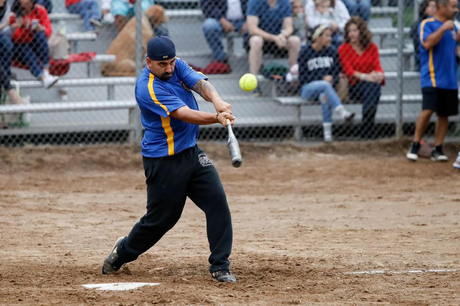 Officer Andrew Tomer drives a hit to right field.