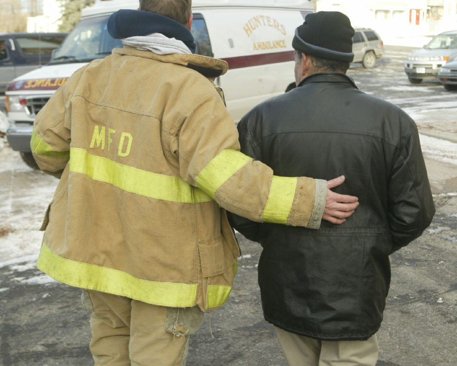 Dep. Fire Marshall Steve Trella, left, consoles home owner Roberto Rosario, right, after his home burned Fri. afternoon, Jan. 16 on Center St.