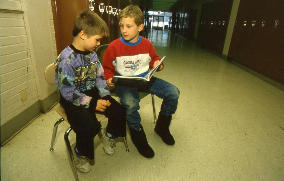 RJ file photo - Danny Berg-Johnson, 6, left, listens as tutor Peter Geer, 8, reads from a baseball book at Parker Farms School in Wallingford Jan. 6, 1994.
