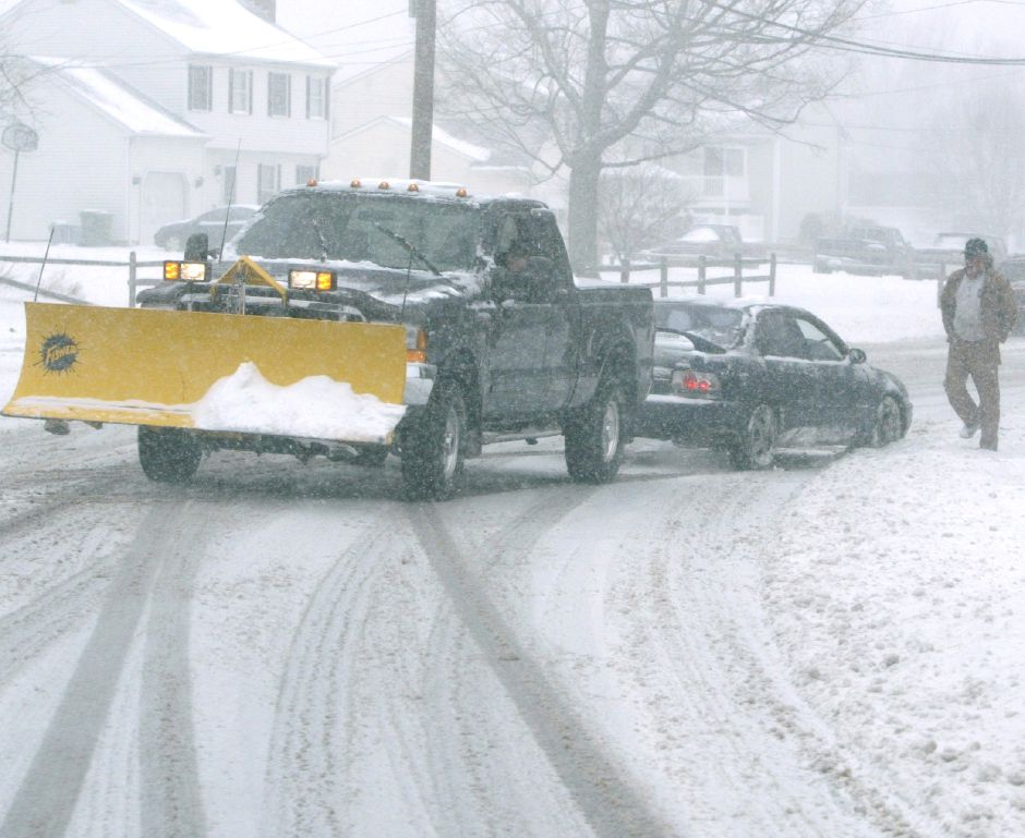 A good samaratin in a truck pulls a car out of a snow bank on Meriden Ave. in Southington on Friday afternoon, March 16, 2007. The car slid into the snow bank on the side of the road and was stuck.