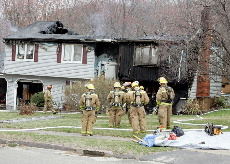 Southington firefighters stand outside a house heavily damaged by fire at 25 Christine Drive in Southington, Friday morning, April 11, 2008. The fire began in the attic causing the roof to collapse shortly after the fire department arrived. (Christopher Zajac/Record-Journal)