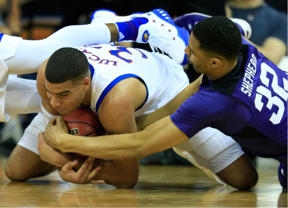 Kansas forward Landen Lucas (33) and TCU forward Karviar Shepherd (32) go to the floor for the ball during first half of an NCAA college basketball game in the quarterfinal round of the Big 12 tournament in Kansas City, Mo., Thursday, March 9, 2017. (AP Photo/Orlin Wagner)