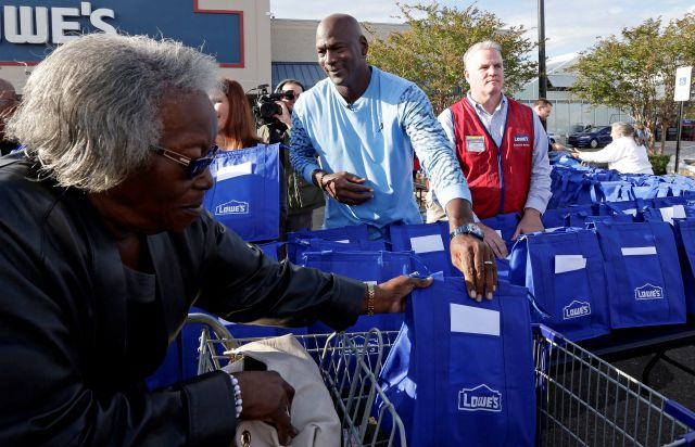 Charlotte Hornets owner Michael Jordan gives a bag of food for Thanksgiving to a woman while greeting members of the community in Wilmington, N.C., Tuesday, Nov. 20, 2018. (AP Photo/Gerry Broome)
