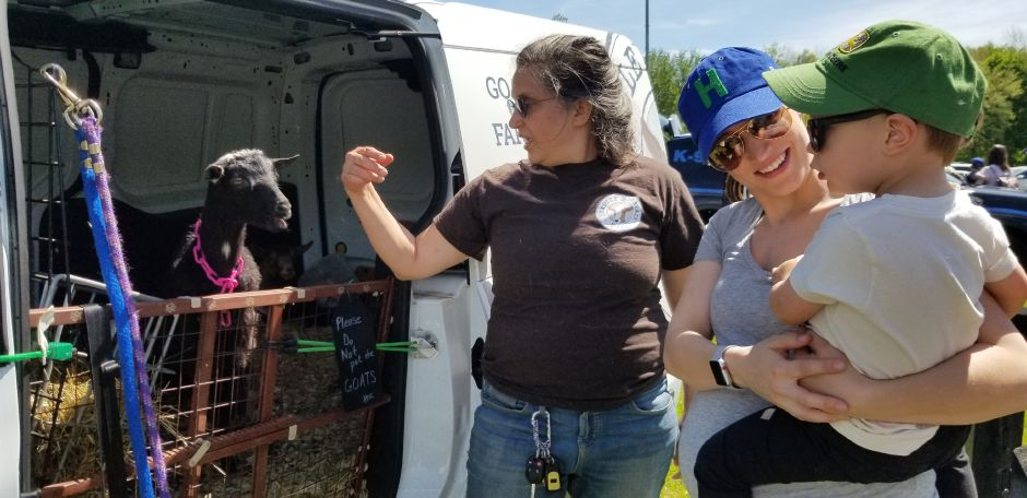 "Anneliese Dadras, owner of Bradley Mountain Farm shows goats to Deeta Gondek and her son Maxwell, 2, in her ""goatmobile"" at the 17th annual Touch-a-Truck event at the Southington Drive-In, at 995 Meriden-Waterbury Turnpike, on Saturday, May 18, 2019. Photos by Jeniece Roman, Record-Journal"