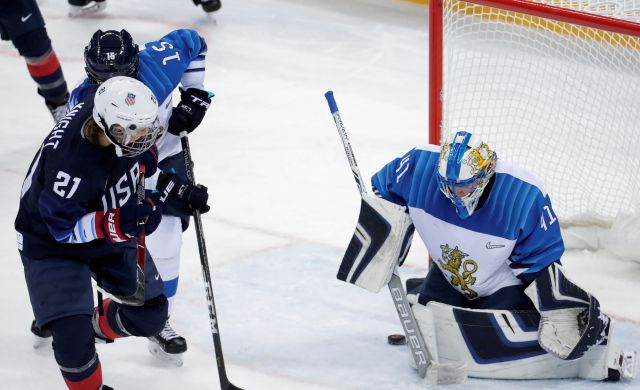 Hilary Knight (21), of the United States, shoots the puck past goalie Noora Raty (41), of Finland, for a goal during the second period of the semifinal round of the women