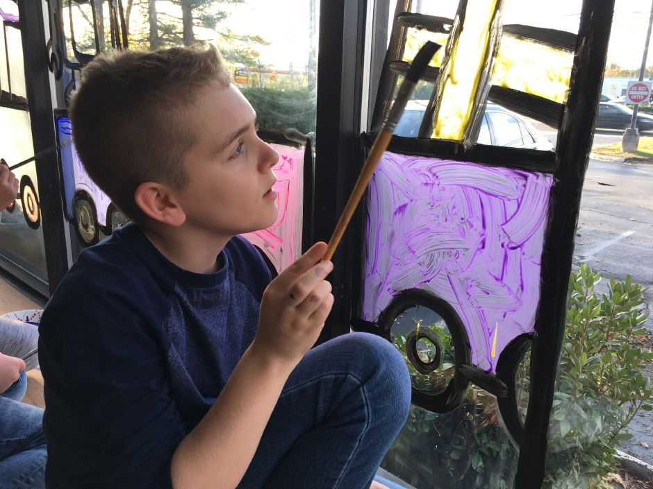 Green Acres Elementary School fifth-grader Tristan Garney, 10, fills the outline of a train car with color. Garney's art teacher, Sheri Schwarz, and several of his classmates decorated the window of Now Security Systems on Thursday, Nov. 2, 2017. | Lauren Takores, Record-Journal