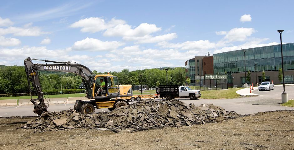 A worker pulls up the parking lot on the north side of Maloney High School as crews continue construction at Maloney High School, Monday, June 13, 2016. | Dave Zajac, Record-Journal