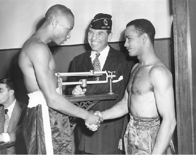 Flash Sebastian, (right), and Ray Robinson, (left), welterweight boxing champion, shake hands after weighing in at the New York State Athletic Commission offices in New York City, on August 29, 1947.  Eddie Eagan, (center), commission chairman, wearing an American Legion cap, looks on.   Sebastian and Robinson are scheduled to meet at Madison Square Garden, in New York, Aug. 29, in a non-title, ten-round bout, which will headline the American League boxing show. (AP Photo/John Rooney