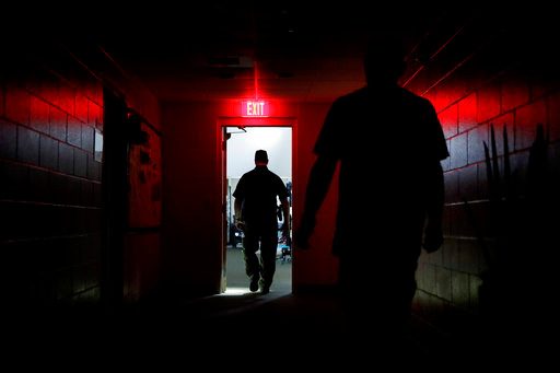 A sheriffs deputy walks through a shelter after the power went out as Hurricane Irma approaches in Naples, Fla., Sunday, Sept. 10, 2017. (AP Photo/David Goldman)