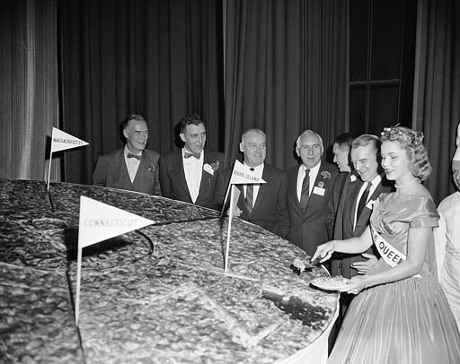 New England governors look on as Apple Queen Marie Kelly cuts a 10-foot apple pie before their meeting at the New England Council conference in Boston, November 17, 1955. The huge pie was made with 285 pounds of apples and has a crust weighing 15 pounds. Left to right are: Governors Christian A. Herter, Mass; Edmund Muskie, Maine; Dennis Roberts, Rhode Island; Joseph B. Johnson, Vermont; Robert P. Lee, of the Conn., Development Commission representing Gov. Abraham A. Ribicoff; Lane Dwinell, New Hampshire and Apple Queen Marie Kelly of Boston. (AP Photo/Frank C. Curtin).
