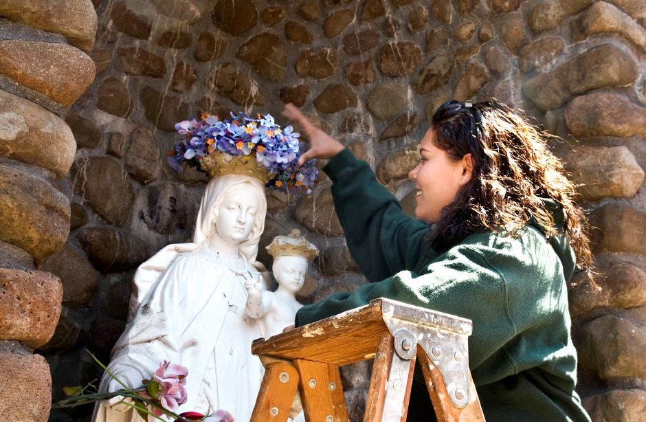 Eighth grader Tyina Melendez places a crown of flowers on a statue of the Virgin Mary at the annual May Crowning Ceremony at Our Lady of Mount Carmel School in Meriden, May 9, 2011. (Sarah Nathan/Record-Journal)