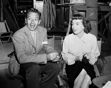 "Academy Award winning star Joan Crawford, with her ever present between-scenes knitting, is visited on the ""Possessed"" set by Paul Henreid. He took time out from his film shoot with Bette Davis only a few stages away to visit with Miss Crawford. This photo is dated September 1, 1946. (AP Photo)"