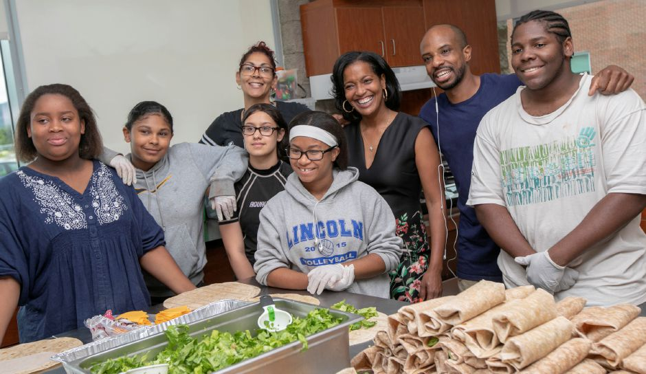 Jahana Hayes, center, takes a group photo with Change the Play members including founder, Jason Teal, second from right, after helping prepare meals for the city's Free Summer Meals program at Maloney High School, Wednesday, August 1, 2018. Hayes, a former National Teacher of the Year, is running against Mary Glassman in the Democratic fifth district primary. Dave Zajac, Record-Journal