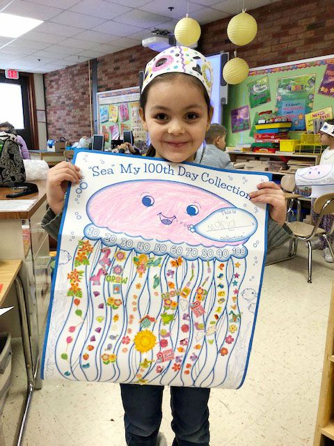 Maria Malave shows off her 100 day hat and 100 day poster.