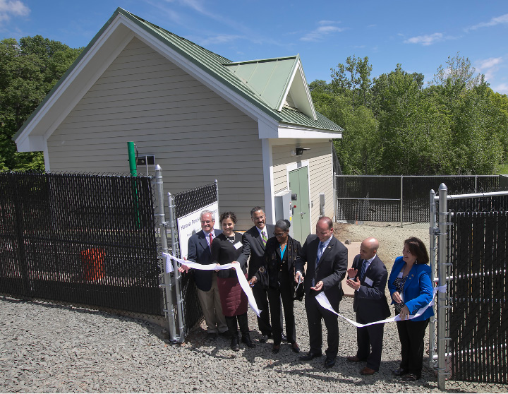 Mayor Kevin Scarpati, center, cuts the ribbon with local and state officials and New England Hydropower Company representatives at Hanover Pond Dam in Meriden, Wednesday, May 24, 2017. Meriden is the first city in the nation to install the technology of ancient Greek scientist Archimedes.    | Dave Zajac, Record-Journal