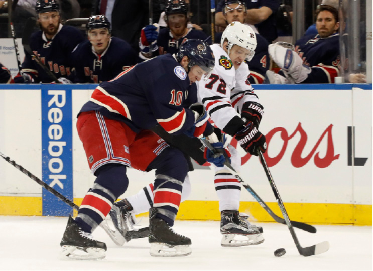 New York Rangers left wing J.T. Miller (10) and Chicago Blackhawks left wing Artemi Panarin (72) battle for control of the puck during the first period of an NHL hockey game Tuesday, Dec. 13, 2016, in New York. (AP Photo/Julie Jacobson)