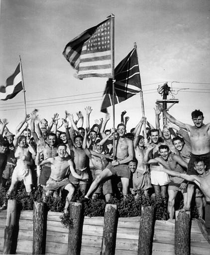 Allied prisoners of war at Aomori camp, near Yokohama, wave flags of the United States, Great Britain and Holland, as they cheer the arrival of their rescuers from the U.S. Navy, on August 29, 1945. (AP Photo)