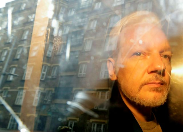 FILE - In this Wednesday May 1, 2019 file photo, buildings are reflected in the window as WikiLeaks founder Julian Assange is taken from court, where he appeared on charges of jumping British bail seven years ago, in London. Swedish prosecutors plan to decide whether they will reopen a rape case against WikiLeaks founder Julian Assange. (AP Photo/Matt Dunham)