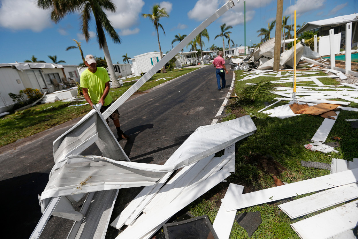 Ralph Bullock kicks up twisted sheet metal in the Hitching Post RV Park, in the aftermath of Hurricane Irma, in Naples, Fla., Tuesday, Sept. 12, 2017. (AP Photo/Gerald Herbert)