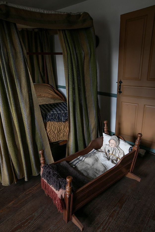 An antique doll sits  in a cradle in a bedroom of the  Solomon Goffe House.