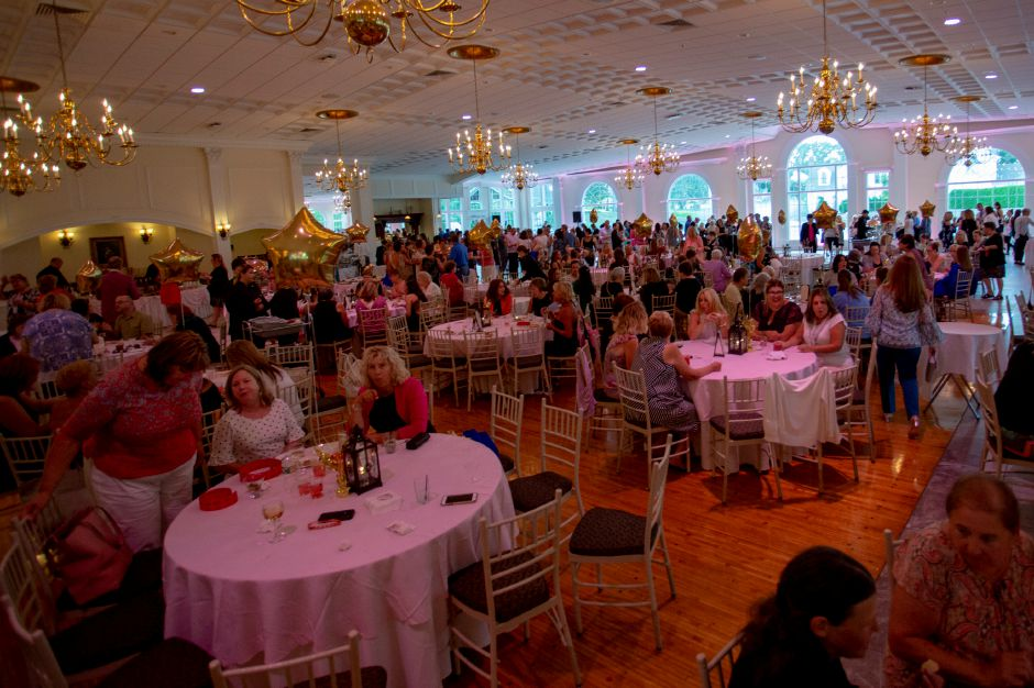 A large crowd mingles under the pink lights during the cocktail hour ahead of the Art Bra 2018 Runway Show and Auction at the Aqua Turf in Southington Aug. 9, 2018. | Richie Rathsack, Record-Journal