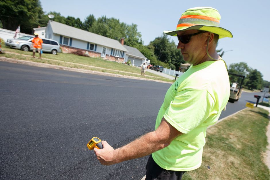 Simon Roby Cheshire Public Works checks the temperature of the asphalt a paving crew from B & W Paving and Landscaping just laid down to resurface Eastgate Drive in Cheshire Monday July 2, 2018 | Justin Weekes / Special to the Record-Journal