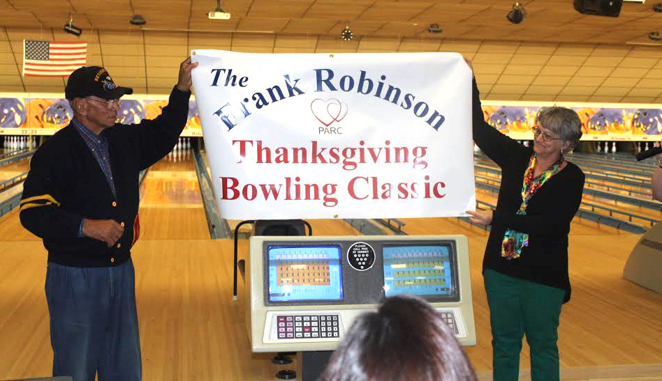 Frank Robinson, and PARC Board of Directors president, June May, hold aloft a sign proclaiming the renaming of the annual bowlathon in Robinson's honor.
