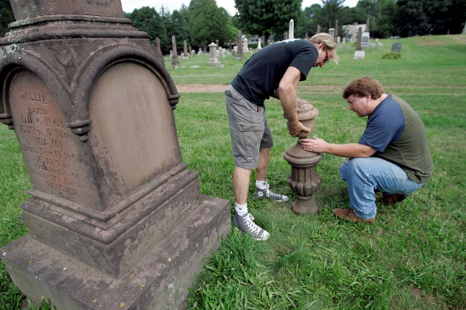 Record Journal Photo/ Johnathon Henninger 8.13.08 - Robert Keeling, a manager at Luby Monuments. right, looks at the top of a cemetery monument belonging to Meriden