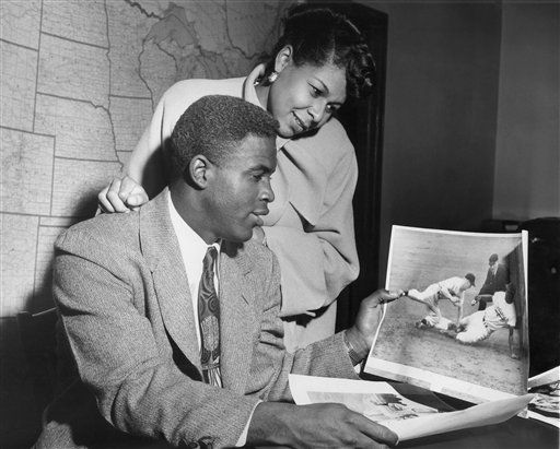 Jackie Robinson, Brooklyn Dodger second baseman, and his wife, view an action picture of the ball player in New York on Nov. 17, 1949. Robinson was named most valuable player in the National League on the basis of his 1949 record. Robinson, first member of the African American race to win this honor in modern major league baseball, polled 12 of 24 firsts, in the competition conducted by 24 members of the Baseball Writers Association, three from each major league city. (AP Photo/Marty Lederhandler)