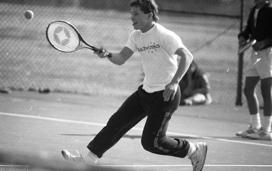 RJ file photo - Ray Konareski, 18, rushes into spring as he works out on the Doolittle Park tennis courts in just a T-shirt. Konareski was playing with Dorrey Worth, March 1989.