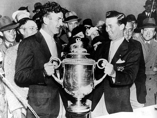 Johnny Revolta, left, receives the PGA Championship trophy from George Jacobus, president of the American Golfers Association, at the Twin Hills Country Club in Oklahoma City, Okla., Oct. 25, 1935. Revolta defeated Tommy Armour, Ill., five and four in 38 holes. Revolta also receives a $1,000 check. (AP Photo)