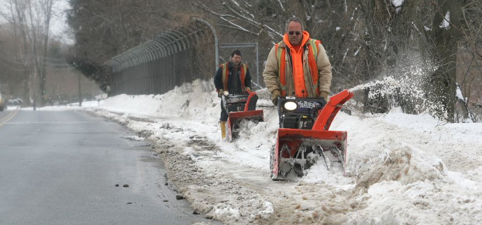 Mike Wrobel, left and Eric Bender, right, work together using snow blowers to clear off a section of Paddock Avenue that goes over the Wilbur Cross Parkway in Meriden Tuesday morning March 1, 2005. The two work for the Meriden Water Division.