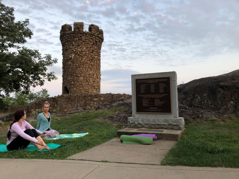 Bhogah Yoga owner Brianne Barrett folds her arms behind her back while demonstrating a yoga pose at a moonlit yoga event at Castle Craig in Meriden. Kristen Dearborn, special to the Record-Journal
