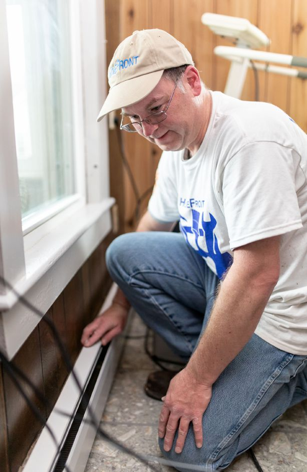 Dwight Davis installs upgrades to a baseboard heater while renovating the home of East Berlin resident Catherine Zabrensky. Dozens of volunteers with the nonprofit HomeFront visited Zabrensky