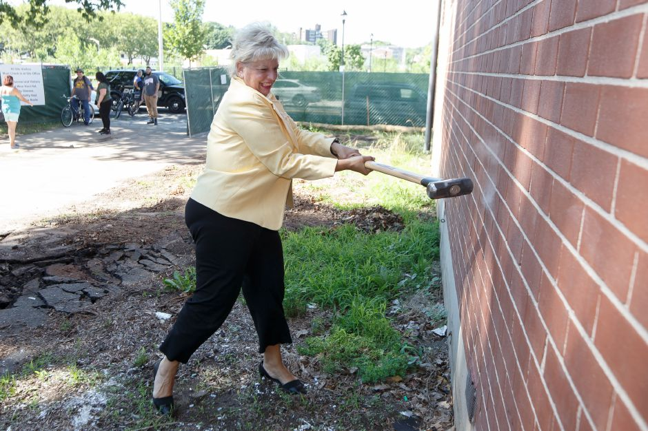 Field Office Director Suzanna Piacentini of HUD Hartford takes a swing at building one Thursday during a ceremony for the demolition of the Mills Apartment Buildings in Meriden August 2, 2018 | Justin Weekes / Special to the Record-Journal