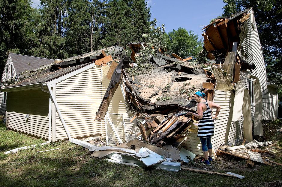 Jen McClure, of Wallingford, salvages items from her home on Grantham Rd Friday, June 26, 2015 after it was heavily damaged by Tuesday