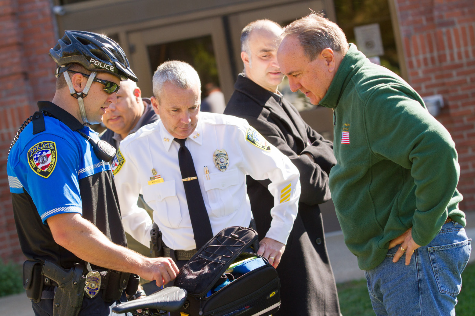 Officer Coleman Turner talks about a new bicycle with Police Chief William Wright and Councilor John Sullivan on Thursday, Oct. 15. The police department recently launched a bike program, giving officers the ability to patrol areas on a bicycle. | Eric Vo / Record-Journal
