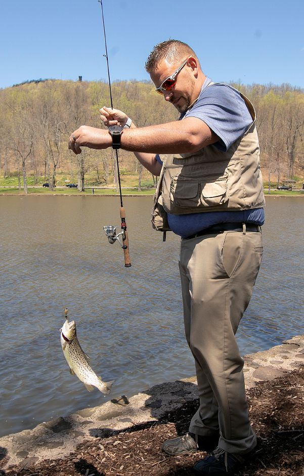 Terry Lewis, of Cromwell, lands a trout while fishing Mirror Lake at Hiubbard Park in Meriden, Tues., Apr. 23, 2019. Dave Zajac, Record-Journal