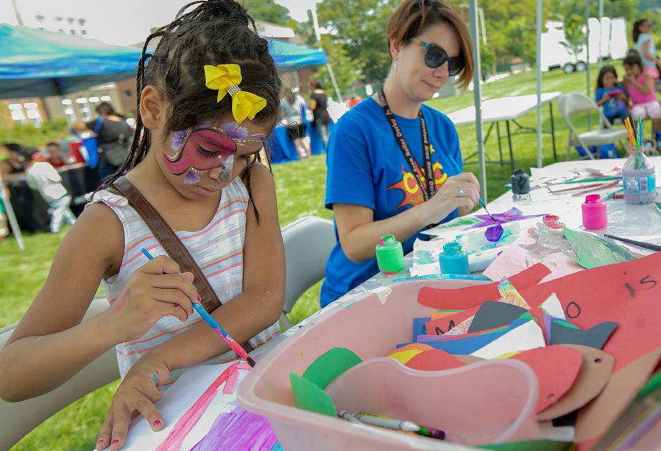 Yehilanis Restituyo, 6, of Meriden, paints a rainbow next to Stephanie Ivers Heine, communications manager for Community Health Center, during the center's health fair on the Meriden Green on Thursday. Community Health Center is celebrating National Health Center week with a series of fairs around the state, including Meriden's event. Dave Zajac, Record-Journal