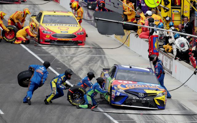 NASCAR Cup Series driver Kyle Busch (18) stops in front of driver Joey Logano (22) for tires and fuel on a pit stop during the NASCAR Brickyard 400 auto race at Indianapolis Motor Speedway, in Indianapolis Monday, Sept. 10, 2018. (AP Photo/Michael Conroy)