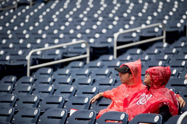 Fans sit in the rain before a baseball game between the Washington Nationals and the New York Mets at Nationals Park, Sunday, Sept. 23, 2018, in Washington. (AP Photo/Andrew Harnik)